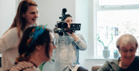 people standing inside room while man standing and holding recording camera during daytime